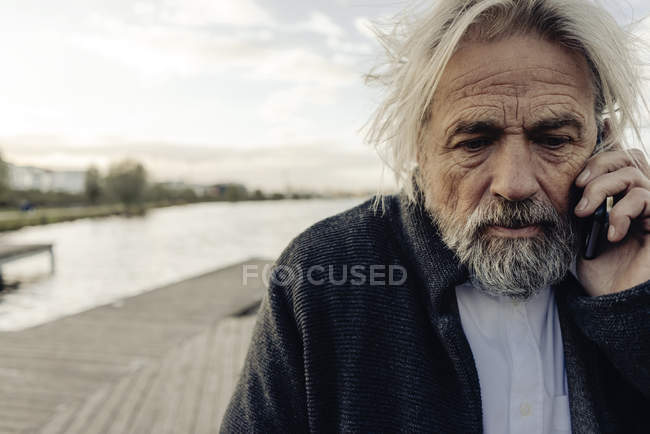 Portrait of serious senior man on cell phone at lake — Stock Photo