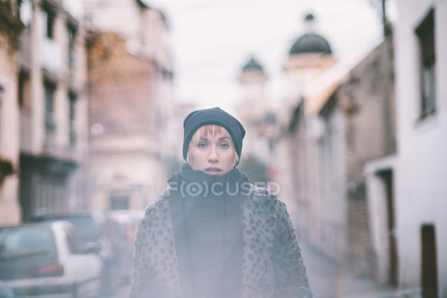 Portrait of fashionable young woman wearing cap and scarf — Stock Photo