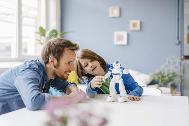 Glücklicher Vater und Sohn spielen zu Hause mit Roboter auf dem Tisch — Stockfoto