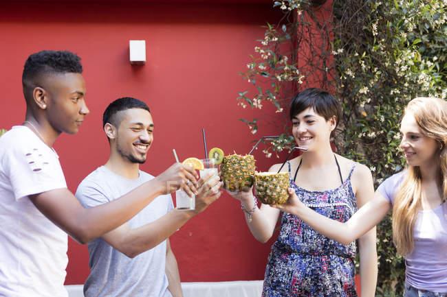 Glückliche Freunde stoßen draußen mit Cocktails an — Stockfoto