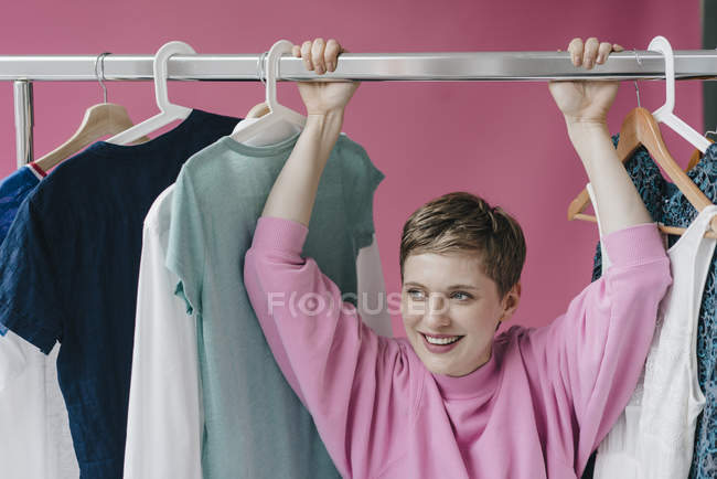 Portrait of smiling woman hanging on clothes rail — Stock Photo