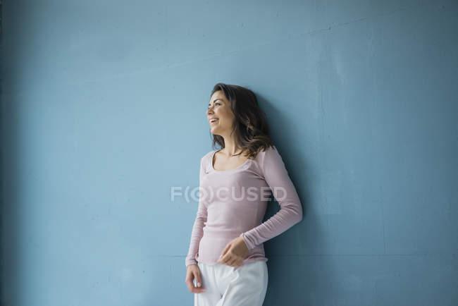 Femme riante adossée au mur bleu — Photo de stock