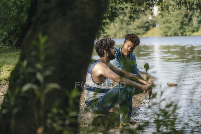 Two multicultural friends relaxing near lake — Stock Photo