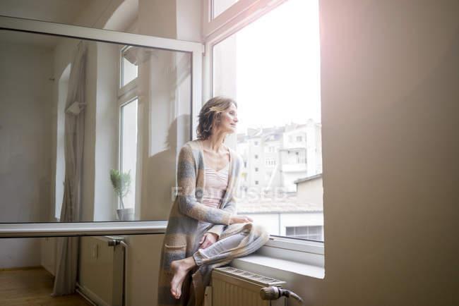 Reife Frau schaut aus dem Fenster — Stockfoto