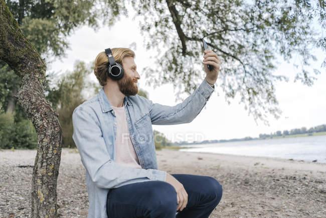 Красивый бородатый мужчина со смартфоном и наушниками на пляже у реки — стоковое фото