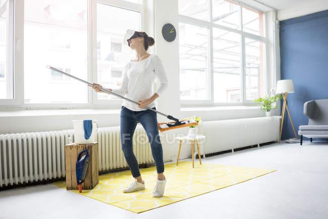 Життєво важливі жінки вдома носіння VR окуляри і витираючи підлогу — стокове фото