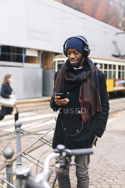 Afrikanischer Amerikaner mit Smartphone und Kopfhörern — Stockfoto