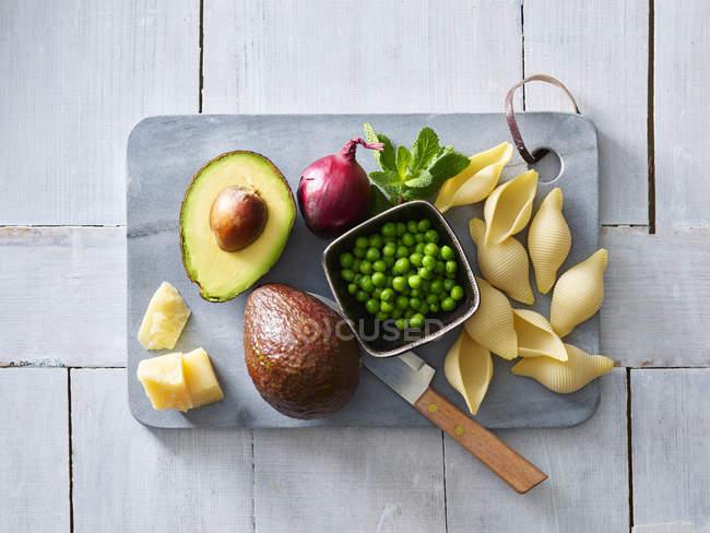 Ingredientes de pasta con salsa de aguacate, guisantes y parmesano - foto de stock