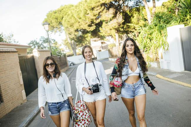 Портрет трех улыбающихся друзей, идущих по жилой улице — стоковое фото