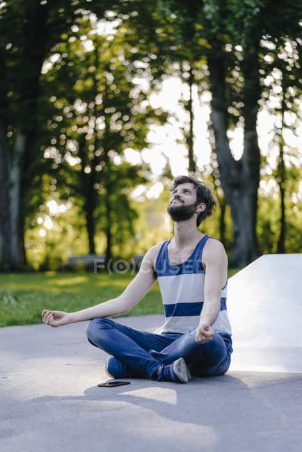 Bello uomo meditando in skatepark — Foto stock