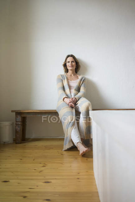 Portrait of smiling mature woman sitting on wooden bench at home — Stock Photo