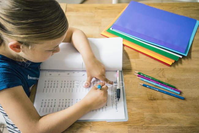 Girl doing homework at table — Stock Photo