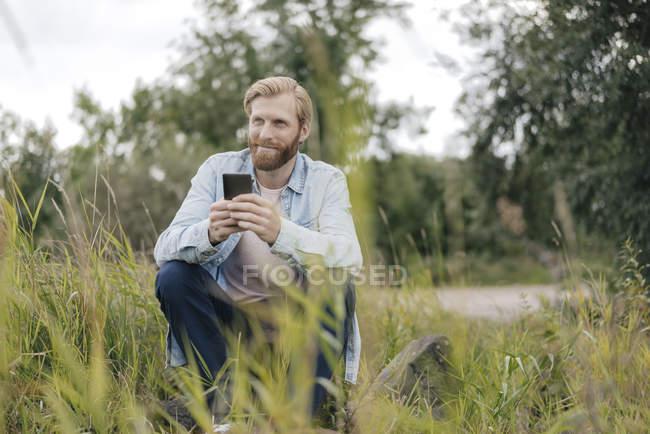 Sorrindo homem usando smartphone na natureza — Fotografia de Stock