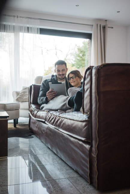 Lächelndes Paar liegt zu Hause auf Couch und teilt Tablet — Stockfoto