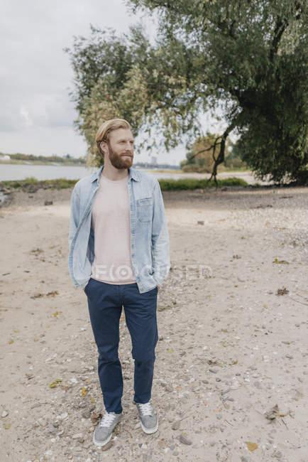 Красивый мужчина ходит по берегу реки и держит руки в кармане, наслаждаясь видом на природу — стоковое фото