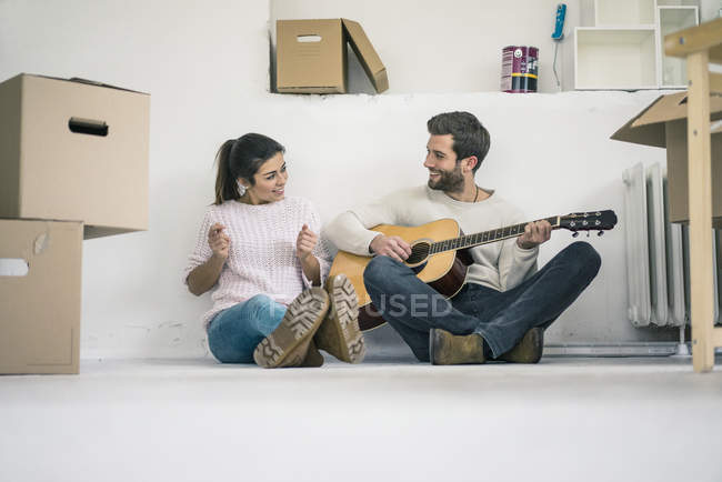 Couple sitting on floor in new home and playing guitar — Stock Photo