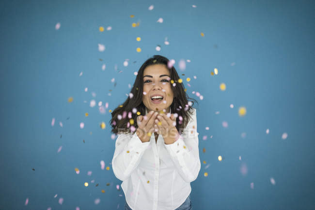 Portrait of laughing woman throwing confetti in air — Stock Photo