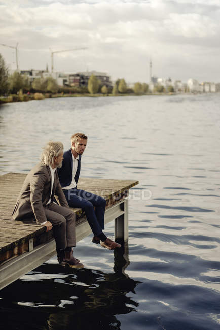 Two businessmen sitting on jetty at lake — Stock Photo