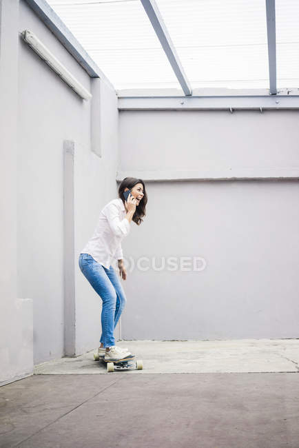 Laughing young woman talking by smartphone and standing on skateboard on terrace — Photo de stock