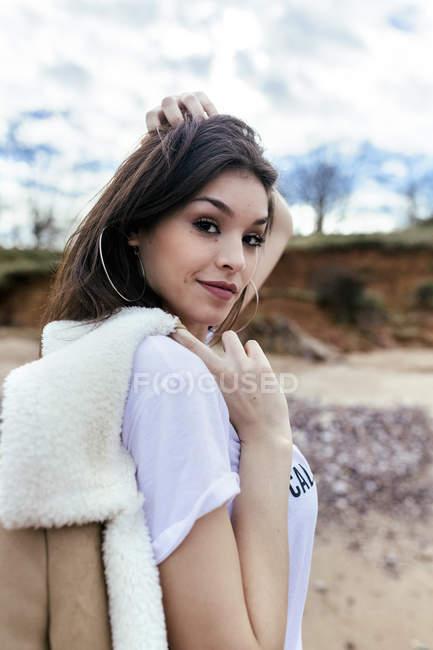 Portrait de belle femme brune sur la plage regardant la caméra et ajustant les cheveux — Photo de stock
