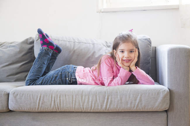 Portrait of smiling little girl lying on the couch — Stock Photo