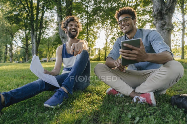 Two happy multicultural friends sitting in park with mobile device and papers — Stock Photo