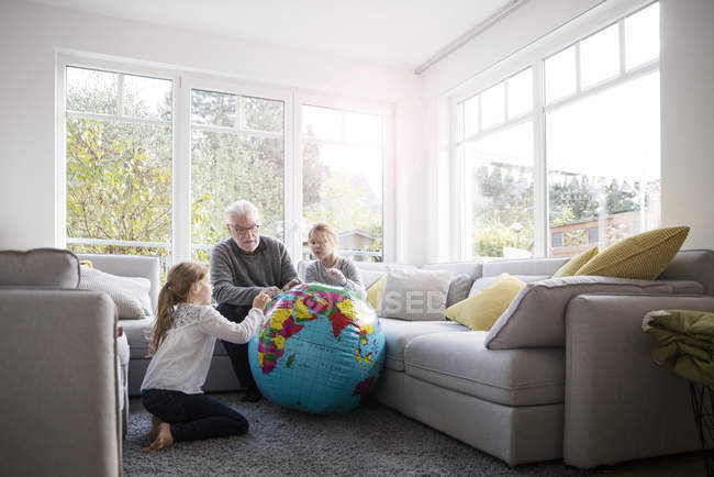 Two girls and grandfather with globe in living room — Stock Photo