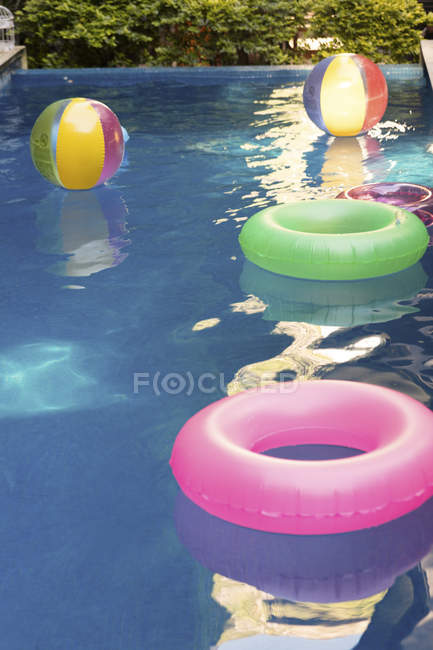 Pooltoys floating on water in swimming pool — Fotografia de Stock