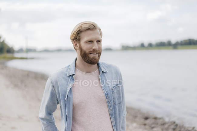 Bello barbuto caucasico sorridente uomo in piedi a riva del fiume — Foto stock