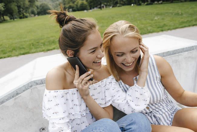 Duas jovens felizes com telefones celulares sentados em um parque de skate — Fotografia de Stock