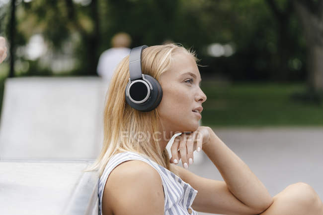 Young woman with headphones listening to music outdoors — Stock Photo