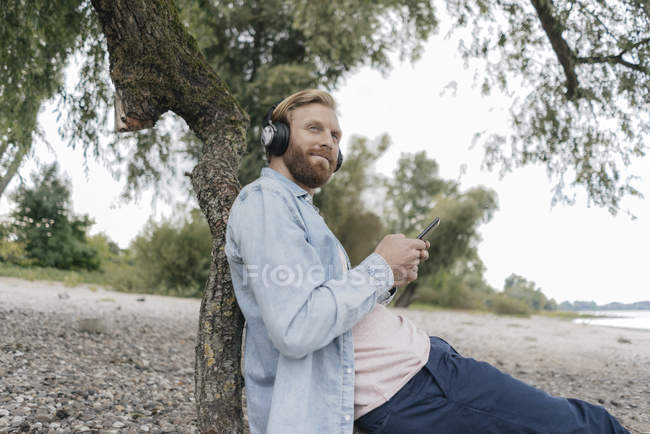 Man listening music with smartphone and headphones on beach under the tree — Stock Photo
