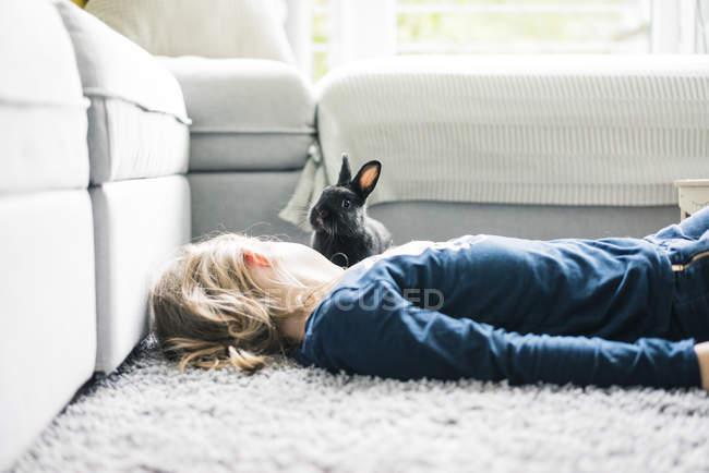 Mädchen liegt mit Kaninchen im Wohnzimmer — Stockfoto