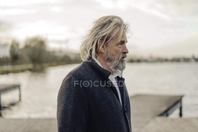 Ritratto di uomo anziano serio al lago — Foto stock