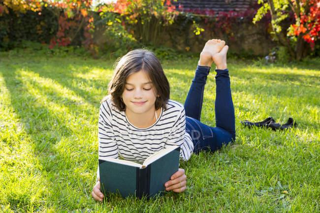 Улыбающаяся девушка лежит на лугу и читает книгу. — стоковое фото