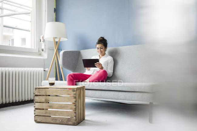Donna sorridente seduta sul divano e utilizzando tablet — Foto stock
