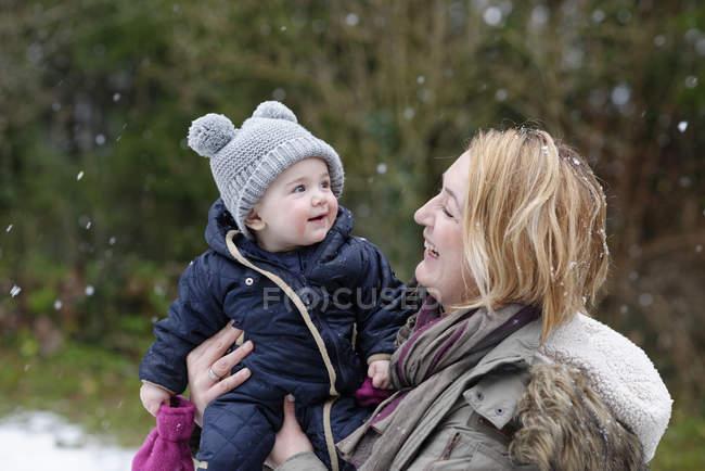 Niña en brazos de su madre viendo copos de nieve por primera vez - foto de stock