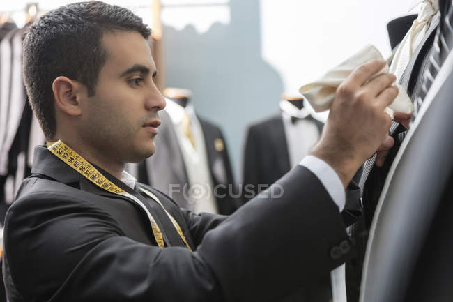 Tailor putting dress handkerchief into tuxedo in tailor shop — стокове фото