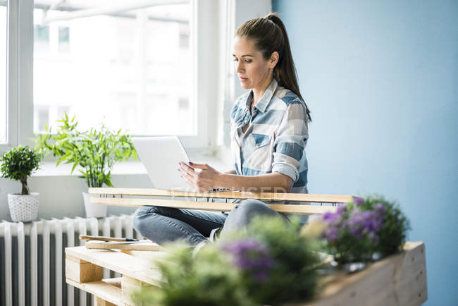 Beautiful woman refurbishing her home with pallets, using laptop — Stock Photo