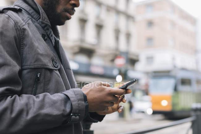 Человек в городе проверяет мобильный телефон — стоковое фото