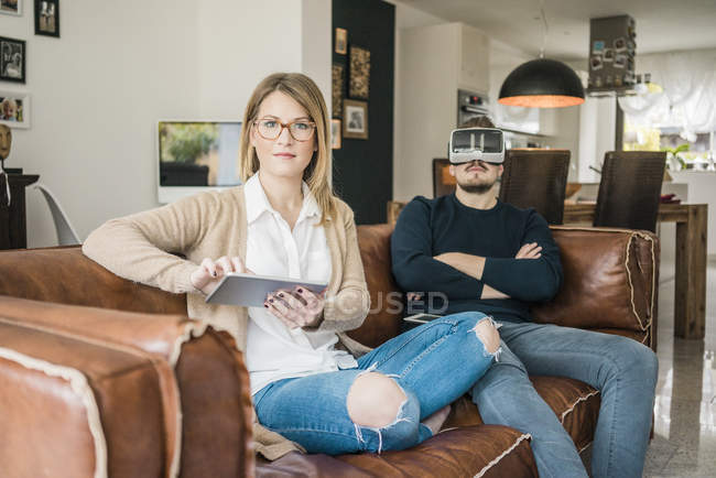 Couple sitting on couch at home with tablet and VR glasses — Stock Photo