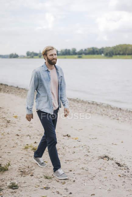 Бородатый кавказский мужчина, идущий по пляжу на берегу реки — стоковое фото