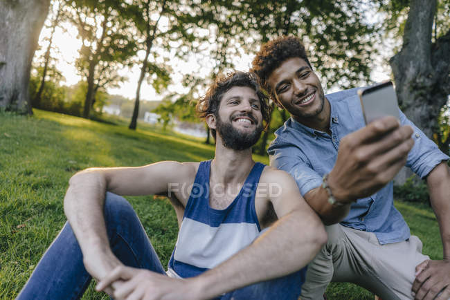Two happy multicultural friends sharing cell phone in park — Stock Photo