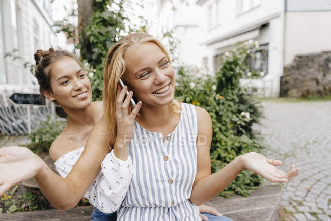 Two happy cheerful young women with cell phone in the city — Stock Photo