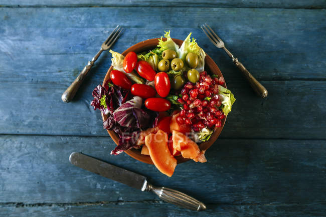 Papaya salad, pomegranate, lettuce, tomato, olives and endive on blue wood — стоковое фото