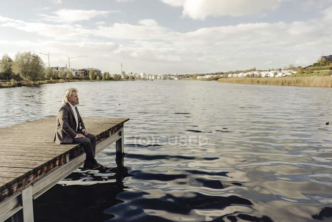 Senior man sitting on jetty at lake — Stock Photo