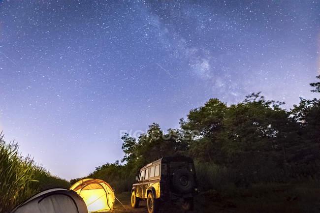 Italia, Piemont, tienda amarilla, landrover, vía láctea y cielo estrellado por la noche - foto de stock
