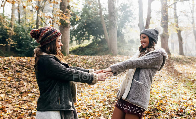 Two pretty women having fun in an autumnal forest — Stock Photo
