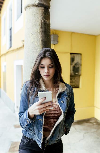 Mujer joven en la ciudad de navegación smartphone - foto de stock