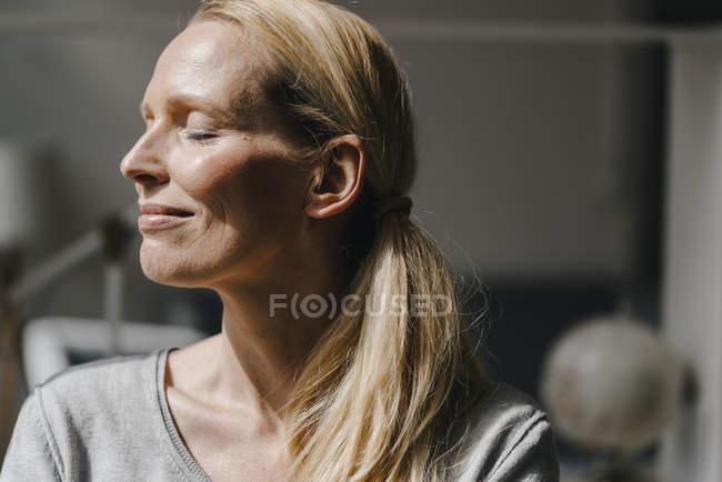 Porträt einer lächelnden Frau im Sonnenlicht — Stockfoto